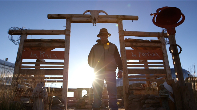 Michael Ruppert in corral, backlit by sun